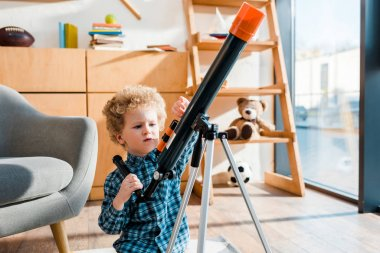 smart child touching telescope near armchair at home