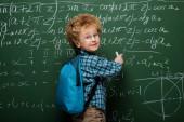 boldog gyerek szemüvegben matematikai képleteket ír a táblára