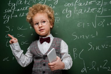 Smart child in suit and bow tie holding smartphone and pointing with finger near chalkboard with mathematical formulas stock vector