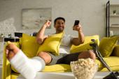 Szelektív fókusz a vidám férfi törött lábbal tv-nézés popcorn mellett az asztalon a nappaliban