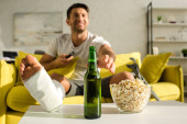 A törött lábú mosolygós férfi szelektív fókusza sörözik popcorn mellett, miközben TV-t néz a kanapén