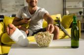 Vágott kilátás mosolygós férfi törött lábbal vesz popcorn mellett sörösüveg fehér tévénézés otthon