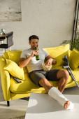 Mosolygós férfi törött lábbal sört iszik és popcornt tart miközben filmet néz a kanapén