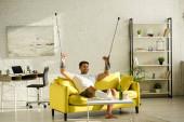 Vidám férfi törött lábbal és mankóval TV-t néz popcorn és sör mellett a nappaliban
