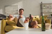 Szelektív fókusz a dühös ember törött lábbal és távirányítóval ül a kanapén sör és popcorn mellett dohányzóasztalon