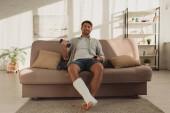 Mosolygós férfi törött lábbal néz TV-t és tartja súlyzó kanapén otthon