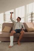Jóképű férfi, gipszkötés edzéssel, súlyzóval és távirányítóval a kanapén