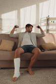 Jóképű férfi törött lábbal edzés súlyzókkal a kanapén a nappaliban