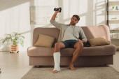 Férfi törött lábbal ül a kanapén és otthon súlyzókkal edz.