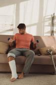 Jóképű férfi törött lábbal edzés súlyzókkal a kanapén otthon