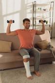 Mosolygós férfi törött lábbal gyakorló súlyzók közelében mankók kanapén