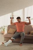 Mosolygós férfi nézi a törött lábát edzés közben súlyzókkal a kanapén