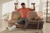 Mosolygós férfi törött lábbal gyakorló súlyzók kanapén a nappaliban