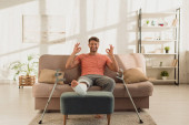 Handsome man with broken leg smiling at camera and showing ok sign on couch