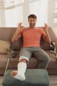 Kilépett férfi törött lábbal ottoman mutatja rendben jel kanapén otthon