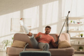Jóképű férfi emelt törött lábbal és mankóval, jóváhagyási jelet mutat a kanapén lévő kamera előtt.