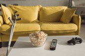 KYIV, UKRAINE - JANUARY 21, 2020: Selective focus of popcorn, remote controller and joystick with crutches near couch in living room