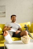 Szelektív fókusz a mosolygó ember lábával gipszkötésben tv-t néz a popcorn mellett a dohányzóasztalon
