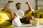 Válogatott fókusz popcorn és törött lába vidám ember távirányítóval kanapén