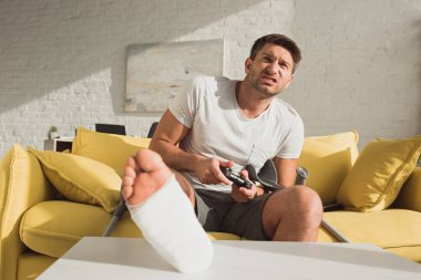 KYIV, UKRAINE - JANUARY 21, 2020: Selective focus of angry man with broken leg playing video game on sofa at home stock vector