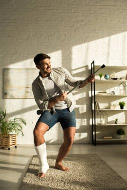 Exited man with broken leg fooling around with crutch in living room