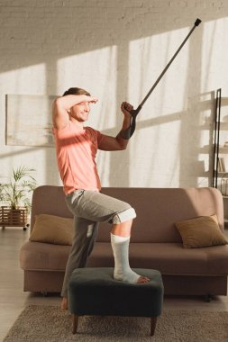 Man with broken leg on ottoman smiling away and holding crutch in sunlit living room