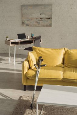 Sunlit living room with crutches near yellow sofa
