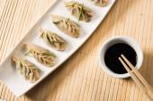 vrchní pohled na lahodné čínské vařené knedlíky na talíři v blízkosti hůlek a sójové omáčky na bambusové podložce