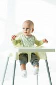 Babysitter etetőszéken, és félrenéz fehér háttér