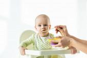 Matka krmení dítě na krmení židle s výživou dítěte na bílém pozadí