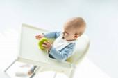 Vysoký úhel pohledu na dítě chlapec drží zelené jablko, zatímco sedí na krmení židle na bílém pozadí