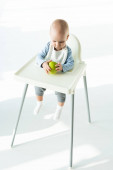 Cute baby holding ripe apple while sitting on feeding chair on white background