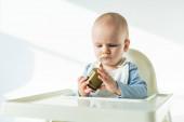 Szelektív fókusz aranyos baba gazdaság üveg növényi bébiétel etetőszék fehér alapon