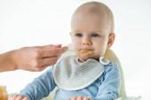 Selektivní zaměření maminka krmení rozkošný chlapeček s ovocem dítě výživy izolované na bílém