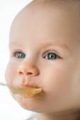Selektivní zaměření roztomilé dítě dívá pryč při krmení s ovocným pyré izolované na bílém
