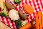 High angle view of jars of vegetable baby food with fresh vegetables and apple on tablecloth on wooden surface
