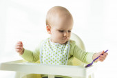 Aranyos baba gazdaság kanál, miközben ül etetés szék fehér háttér