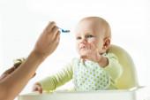 Selektivní zaměření roztomilé dítě tahání ruku v ruce s lžíce dětské výživy izolované na bílém