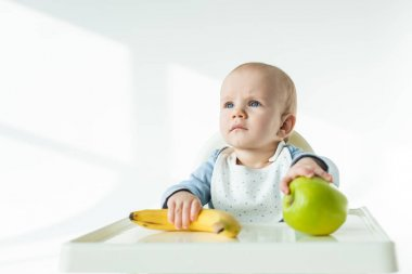 Adorable baby holding ripe banana and apple on table of feeding chair on white background stock vector