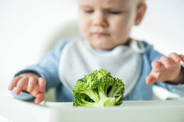 Selective focus of piece of broccoli on table near baby on feeding chair isolated on grey stock vector