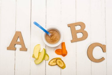 Top view of baby food with spoon and ingredients near wooden letters on white wooden background stock vector