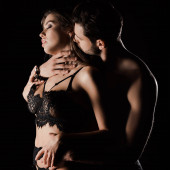 shirtless man kissing seductive woman in underwear isolated on black