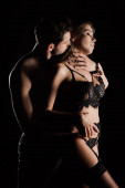 shirtless man kissing seductive woman with closed eyes in lace underwear isolated on black