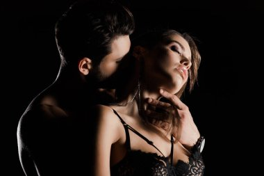 muscular man kissing seductive woman with closed eyes isolated on black