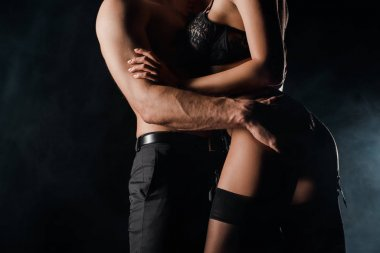 cropped view of hot couple hugging on black with smoke
