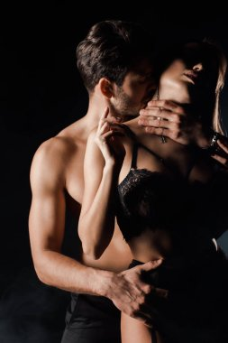 shirtless man kissing seductive woman in lingerie on black with smoke