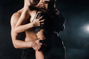 cropped view of shirtless man touching seductive woman in lace lingerie on black with smoke