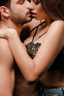 side view of muscular man kissing woman in lace bra on black