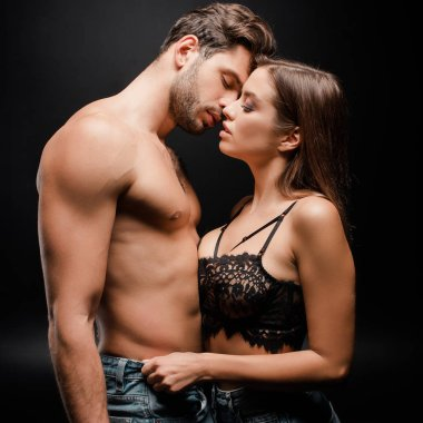 side view of muscular man kissing with woman in lace bra on black