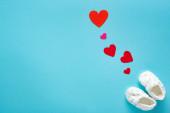 Horní pohled na dětské botičky s papírovými srdíčky na modrém pozadí, koncept dne matek